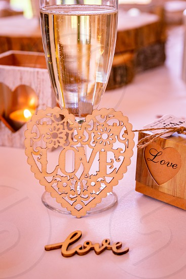 Love concept.  Champagne glass with love text and heart shapes on accessories in a wedding setting photo