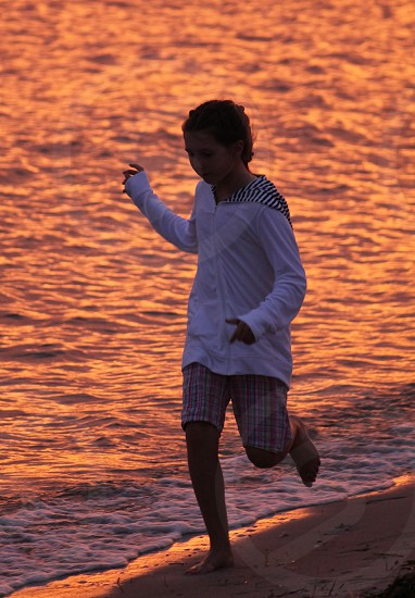 Catching my girl jogging along the shore at sunset photo