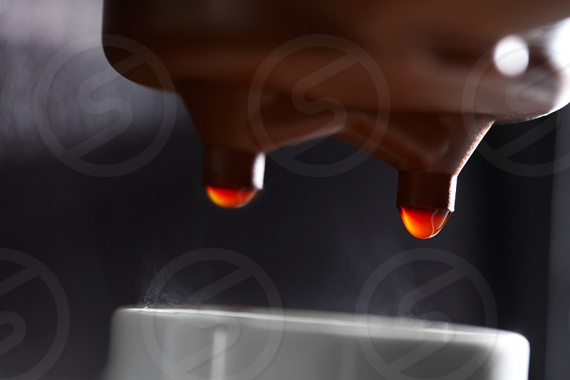 Macro photo of making coffee in the coffee machine. Drops of coffee dripping into the cup photo