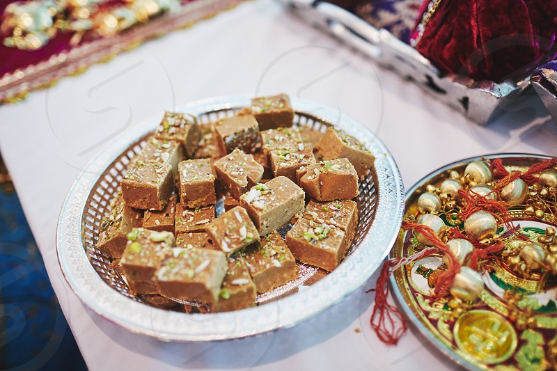 Variety of Indian sweet dish dessert made from bean on the weave wooden table To be served on indian wedding ceremony photo