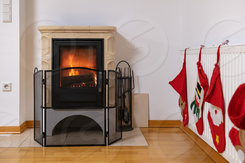 Tiled stove with fire burning inside cosy and warm interior scene heating in winter Christmas decoration on the wall photo