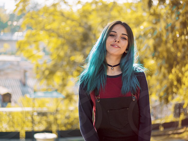 Street punk or hipster girl enjoying empty old European street. Portrait of teen girl with blue dyed hairpiercing in noseviolet lenses and unusual hairstyle. photo