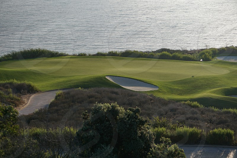 An oceanfront golf course in southern California has a neatly groomed green in late afternoon sunlight bordered by sand traps and rough vegetation against the blue Pacific Ocean. photo