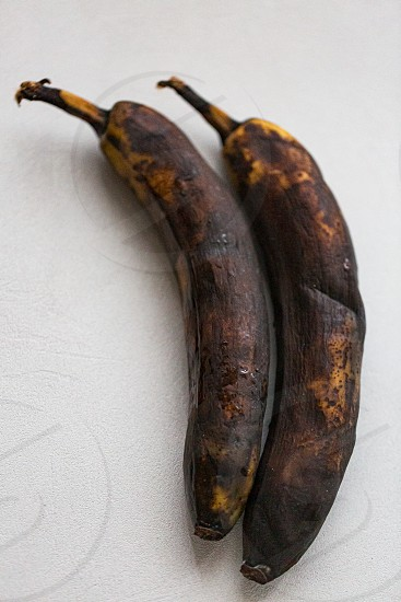 Dried unhealthy banana on white background. Trendy spoiled organic fruits. Ugly fruit. Vertical oriented. photo