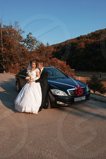 wedding coupe leaning on black car photo