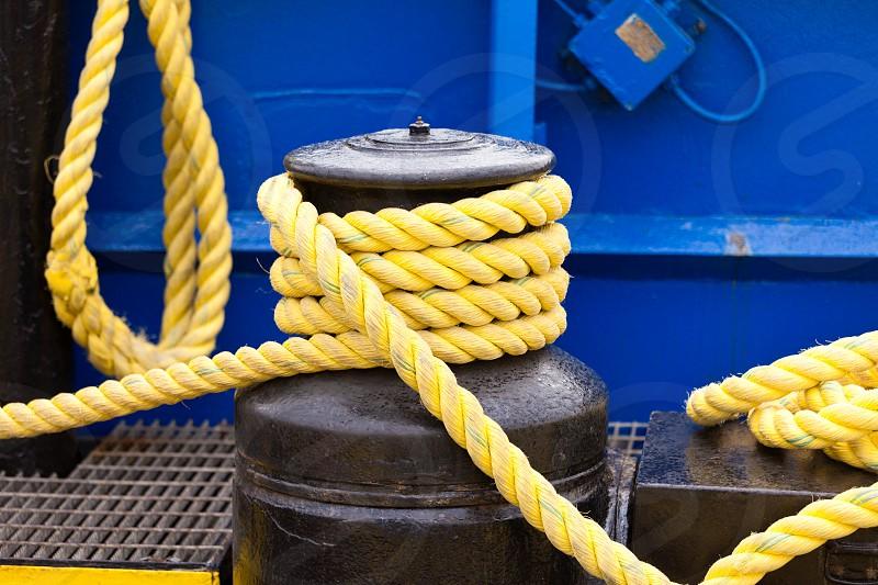 Yellow mooring line coils on black winch photo