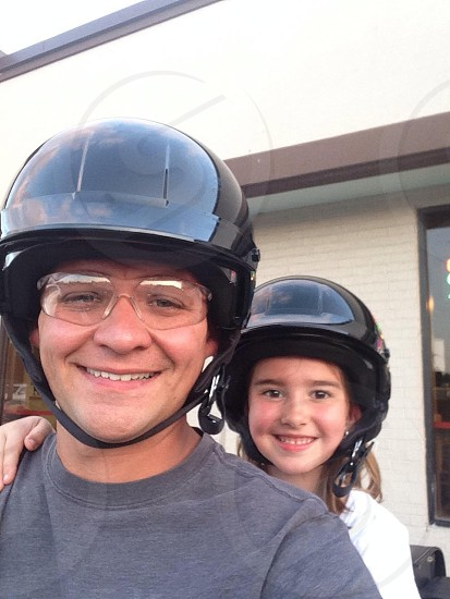 man wearing black motorcycle helmet and girl wearing black motorcycle helmet photo