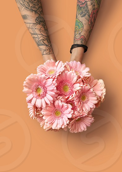 Hands of a woman with a tattoo hold a beautiful bouquet with pink gerberas on an orange background. Spring concept. Happy Mother's Day. Flat lay photo