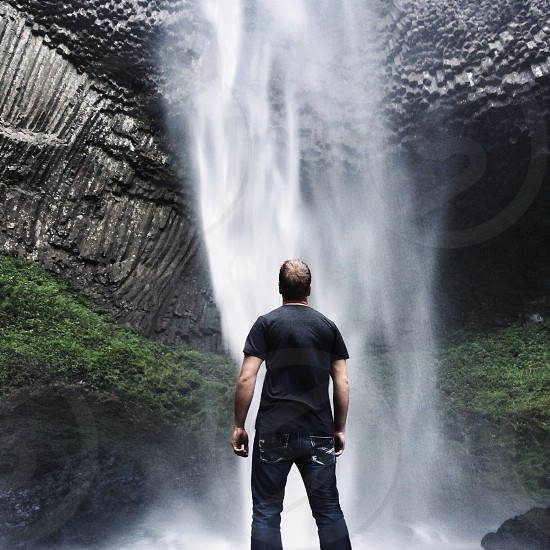 man in black t shirt and blue denim jeans looking on the water falls photo