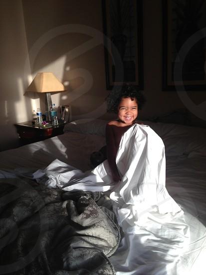 child on white bed holding white blanket photo