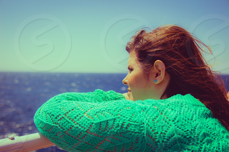 Woman leans on the railing and looking out to sea on the horizon photo