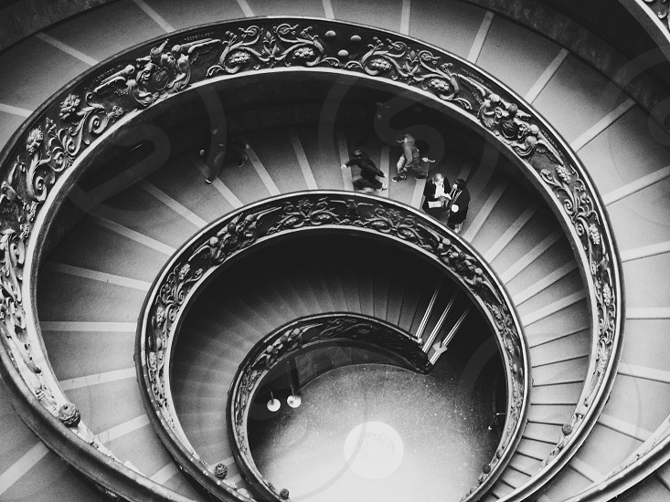 people walking on concrete spiral stairs case in grayscale photo