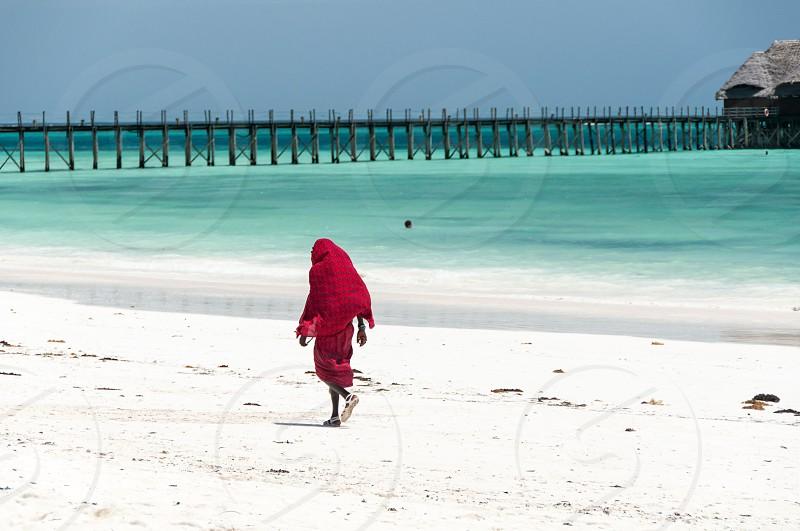 Zanzibar - Tropical island in the Indian Ocean - Masai on white beach and wooden pier photo