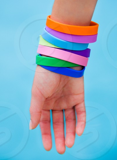 right human wrist with 8 orange purple blue green yellow and pink silicone bracelet photo