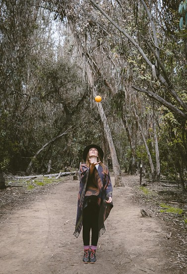 woman with brown and blue scarf thrown orange surrounded by trees photo