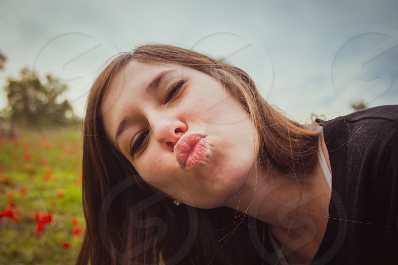Young woman making duckface kiss while taking selfie picture with her smartphone or camera in field of red poppies. She having fun doing silly and funny to the camera. photo