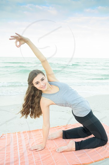 A young woman doing yoga on the beach. photo
