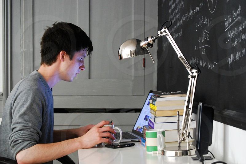 Young man working on laptop computer. photo
