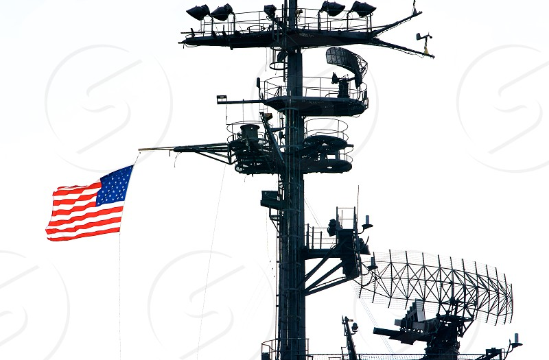 american flag waving in the mast of a aircrafts carrier photo
