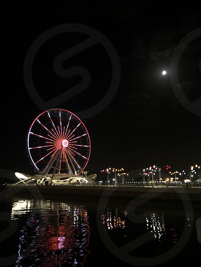 Circle in the sky (moon) and circle on earth (Ferris wheel). Sometimes the connections do not go through lines but through circles. Ferris wheel in the evening. From a series of panorama Baku. photo