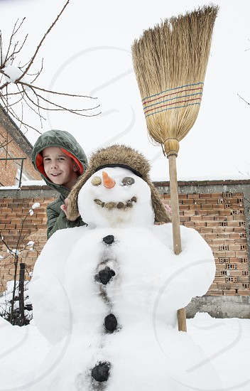 Snowman and child in the yard. Winter photo