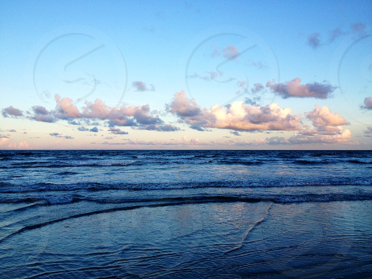 ocean shore under blue and white cloudy sky during daytime photo