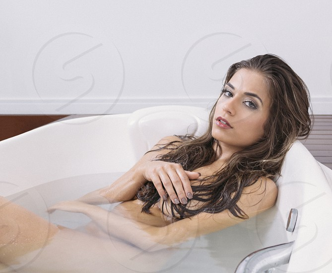 nude woman in white bathtub covering her private parts photo