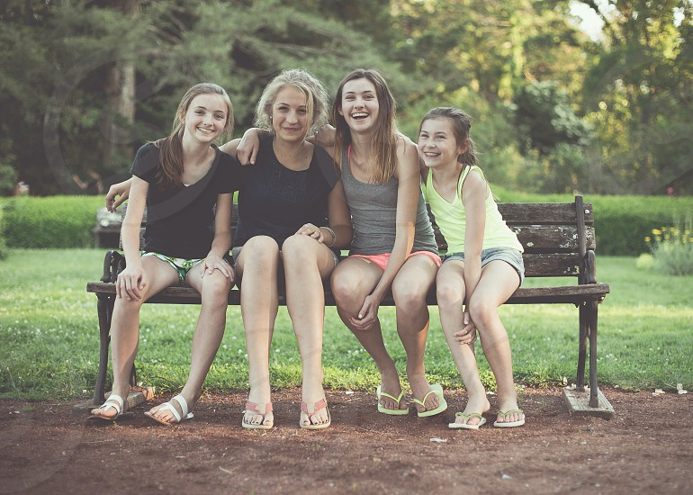 4 girls sit on a bench in a park. photo