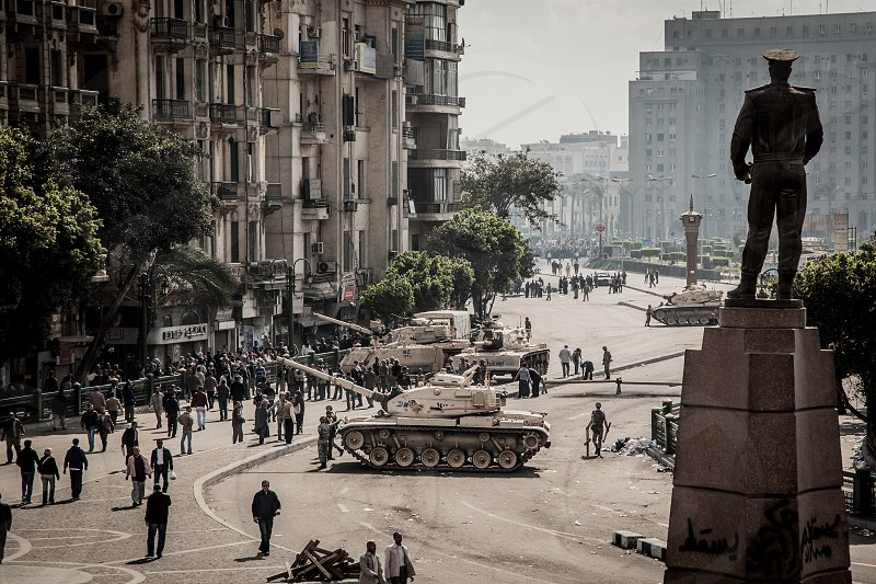 This is a photo taken from the corner of Tahrir Square on the 30th of January 2011 when the first wave of the revolution had defeated the police force causing them to retreat and forcing the military to step in. As seen in the photo tanks were placed at the entrances to the square. In the foreground there is a statue of one of the military generals known for his participation in the 6th of October war. photo