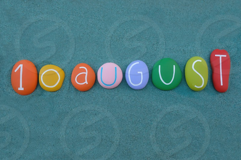 10 August calendar date composed with multi colored stones over green sand photo