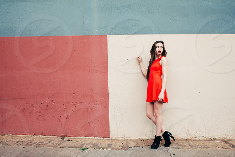 woman in a red halter dress standing before a white painted wall photo