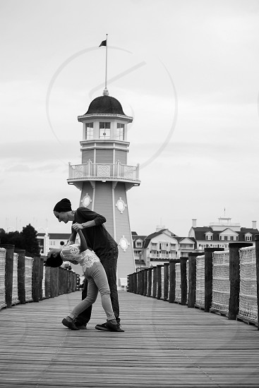 greyscale photo of couple dancing on foot bridge in front of light house photo