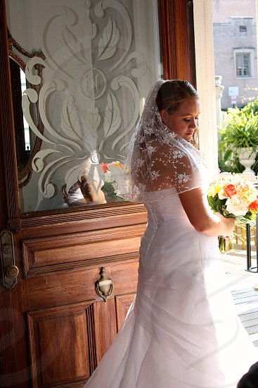 woman wearing white wedding gown holding beige and red flower bouquet photo