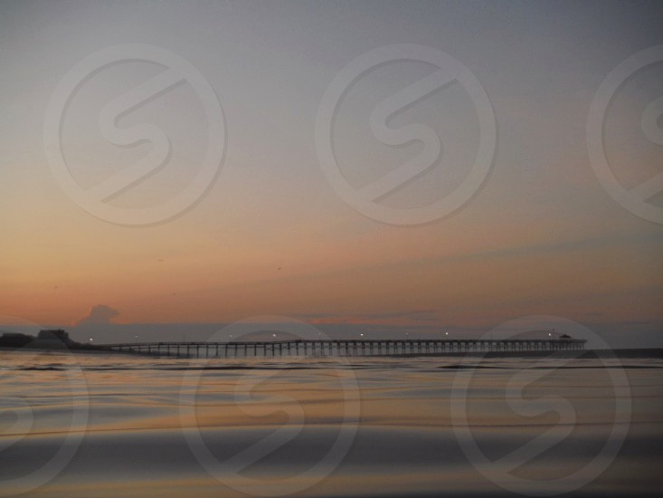 an ocean pier at sunrise with the water in foreground photo