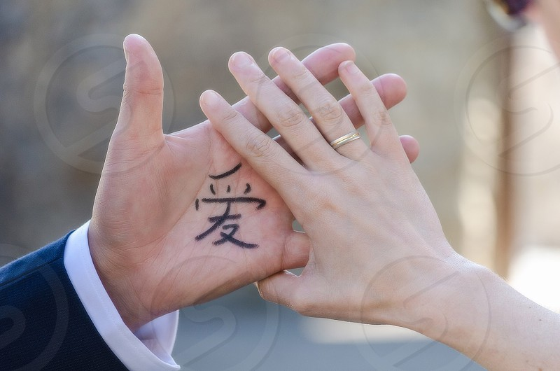 right woman's hand with gold ring and left man's hand with chinese character photo