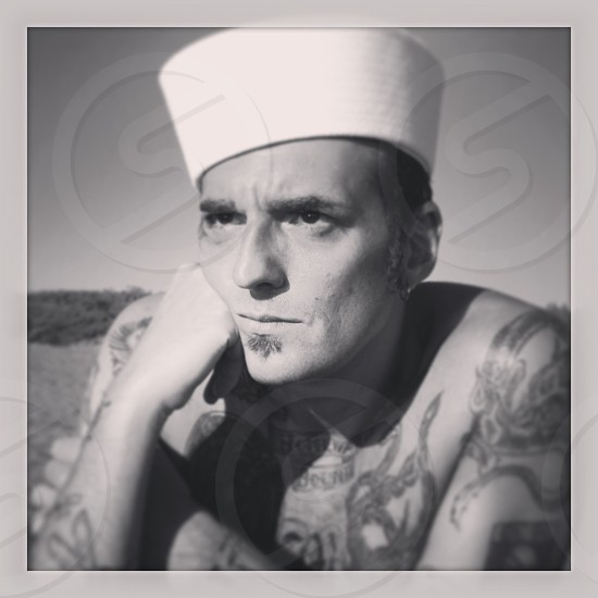 man with body tattoos wearing white hat photo