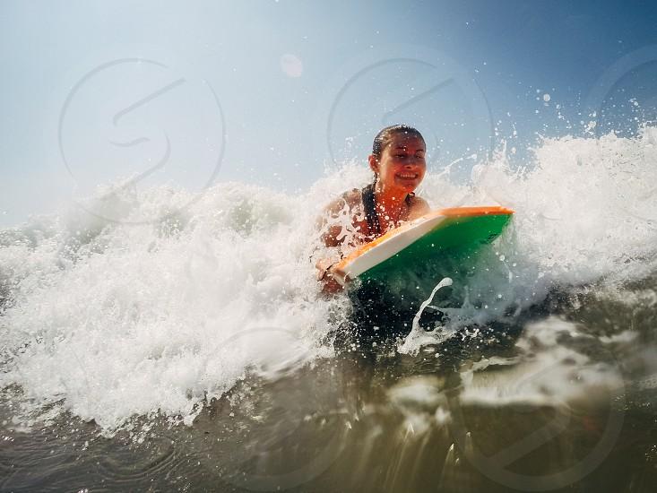 A teenage girl bodyboards in ocean waves. photo
