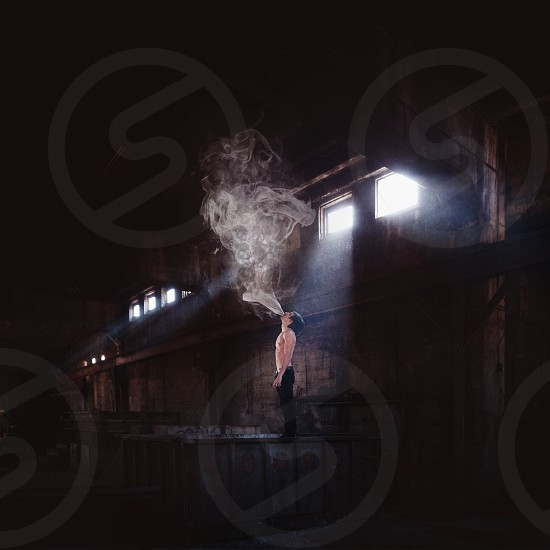 man standing on container blowing smoke into air photo