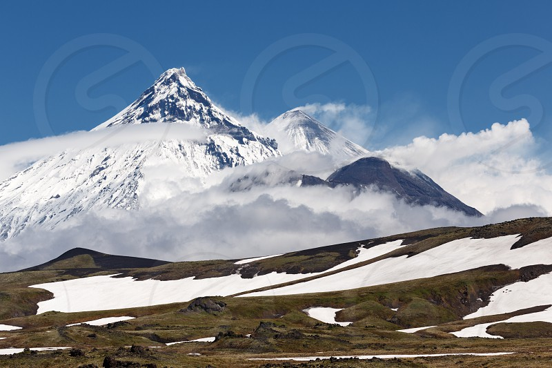 Picturesque mountain landscape of Kamchatka: view on Kamen Volcano active Klyuchevskoy Volcano and active Bezymianny Volcano on a sunny day. Russia Far East Kamchatka. photo
