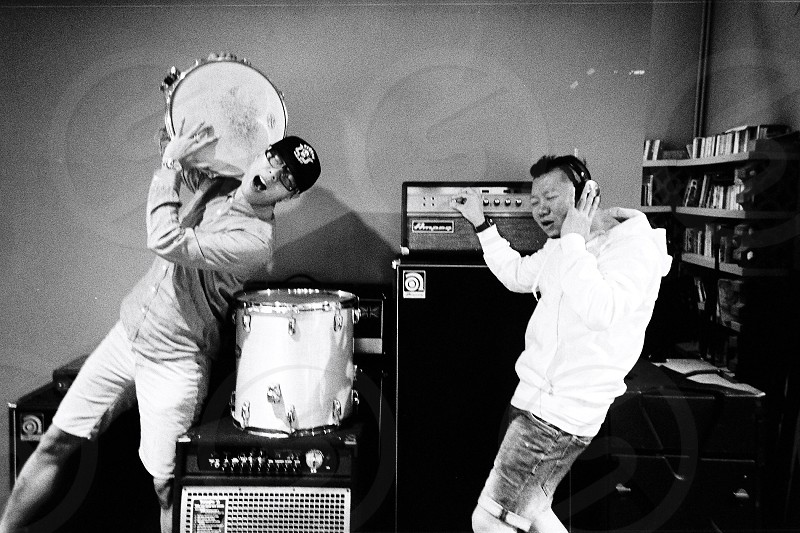 grayscale photography of two men in studio with percussion instruments and amplifier photo