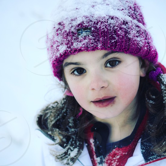 photography of girl wearing purple knit cap cover of snow photo