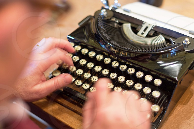 Person typing with hands on typewriter. photo