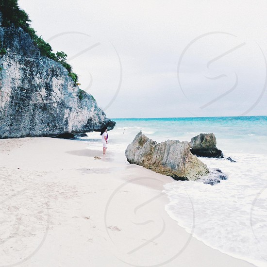 view of woman standing on white sand photo