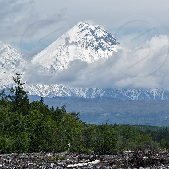 Mountain landscape: beautiful summery view of Kamen Volcano on a cloudy day. Russia Far East Kamchatka Peninsula Klyuchevskaya Group of Volcanoes. photo