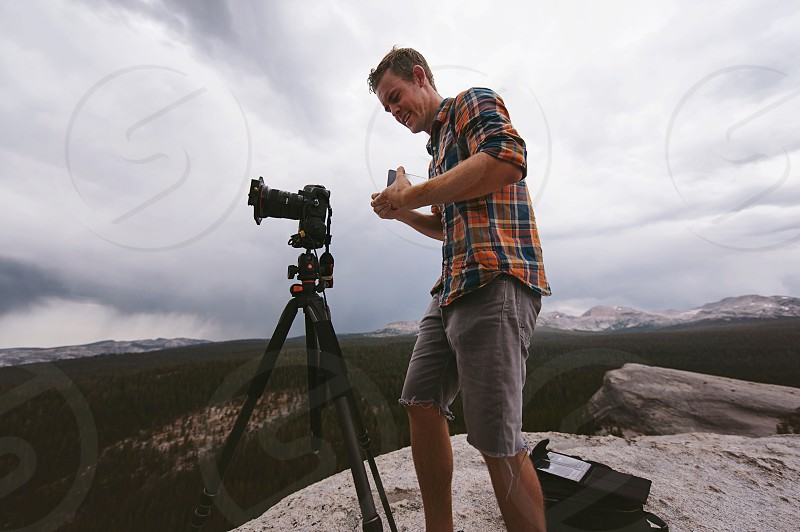 man in orange white and blue plaid dress shirt and grey shorts standing in front of camera on tripod photo
