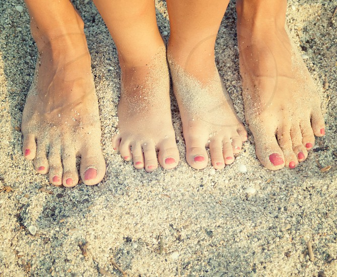 feet of child and mom in the sea sand photo