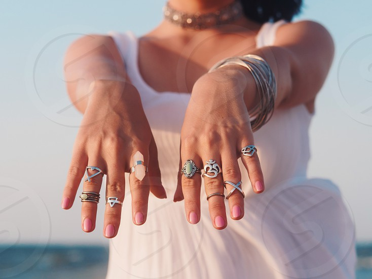 close up hands with boho gypsy silver accessories. Woman standing on the beach at summer near sea. photo