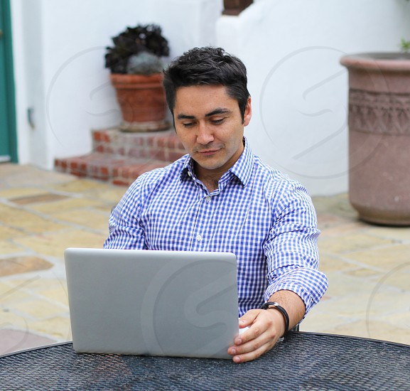 Working on a laptop outdoors. Spanish-style decor. photo