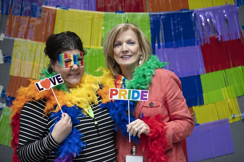 Two women in rainbow feather boas for pride event photo