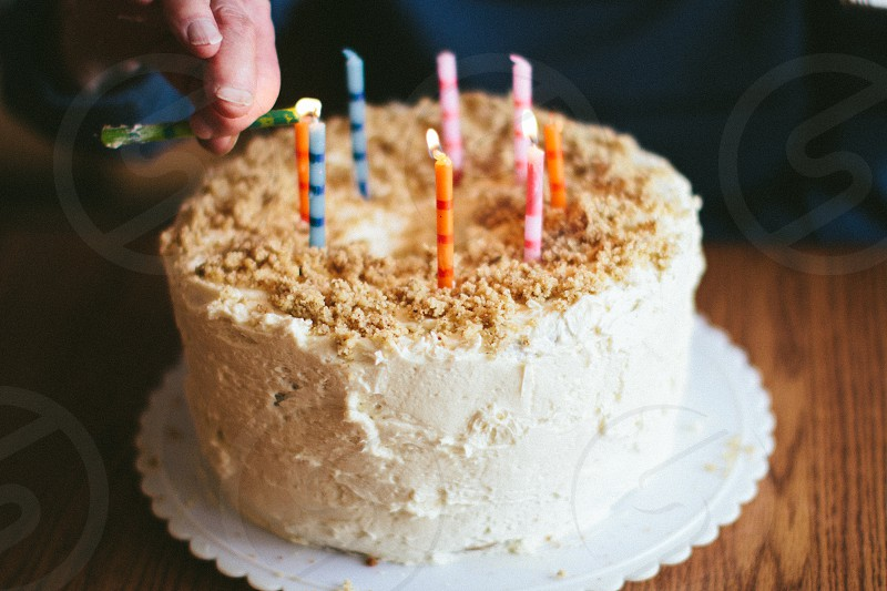 white round birthday cake with brown crumbs top and candles photo